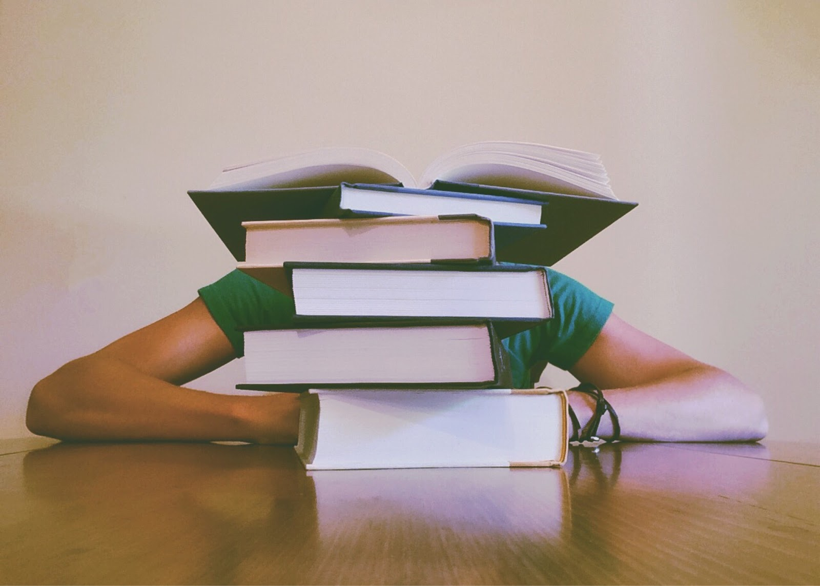 Person behind pile of books