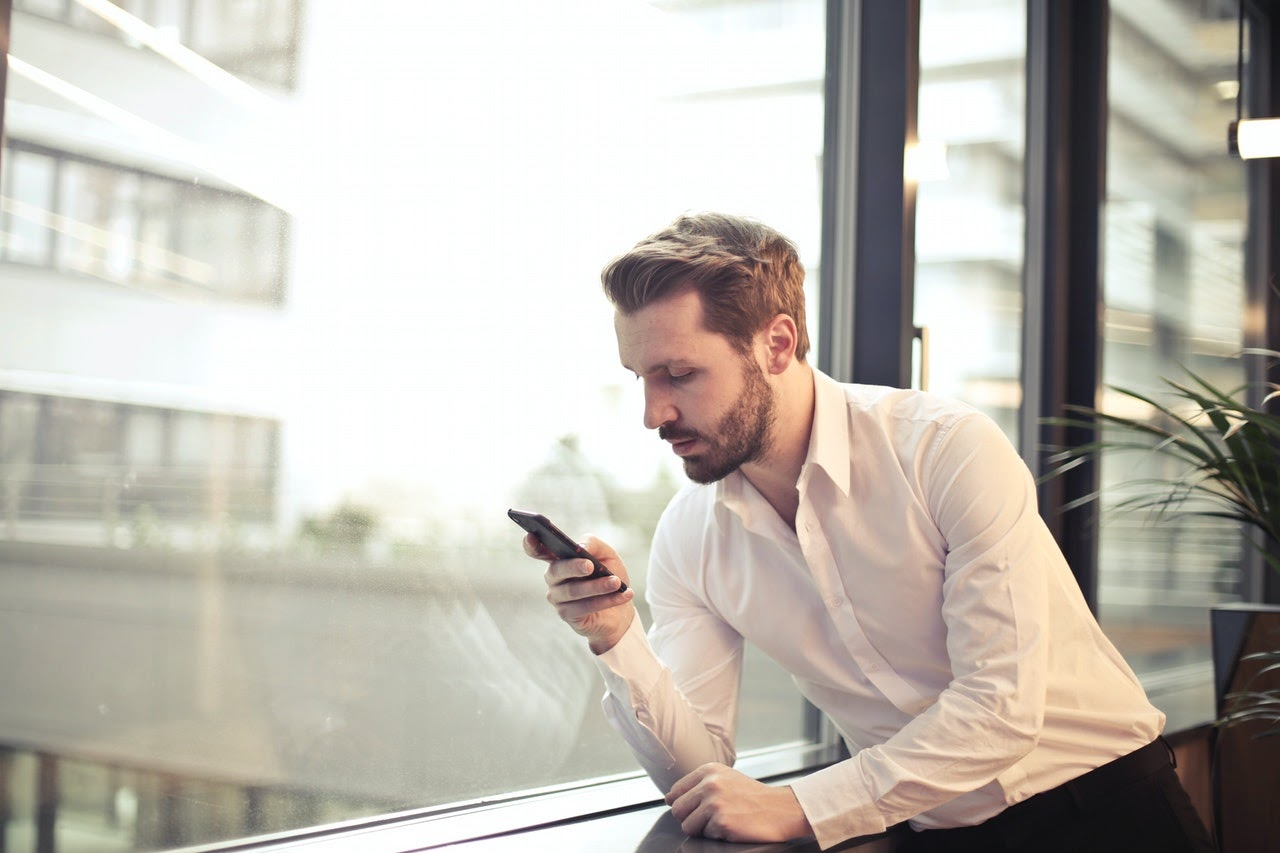 Man leaning against a window looking at a smartphone