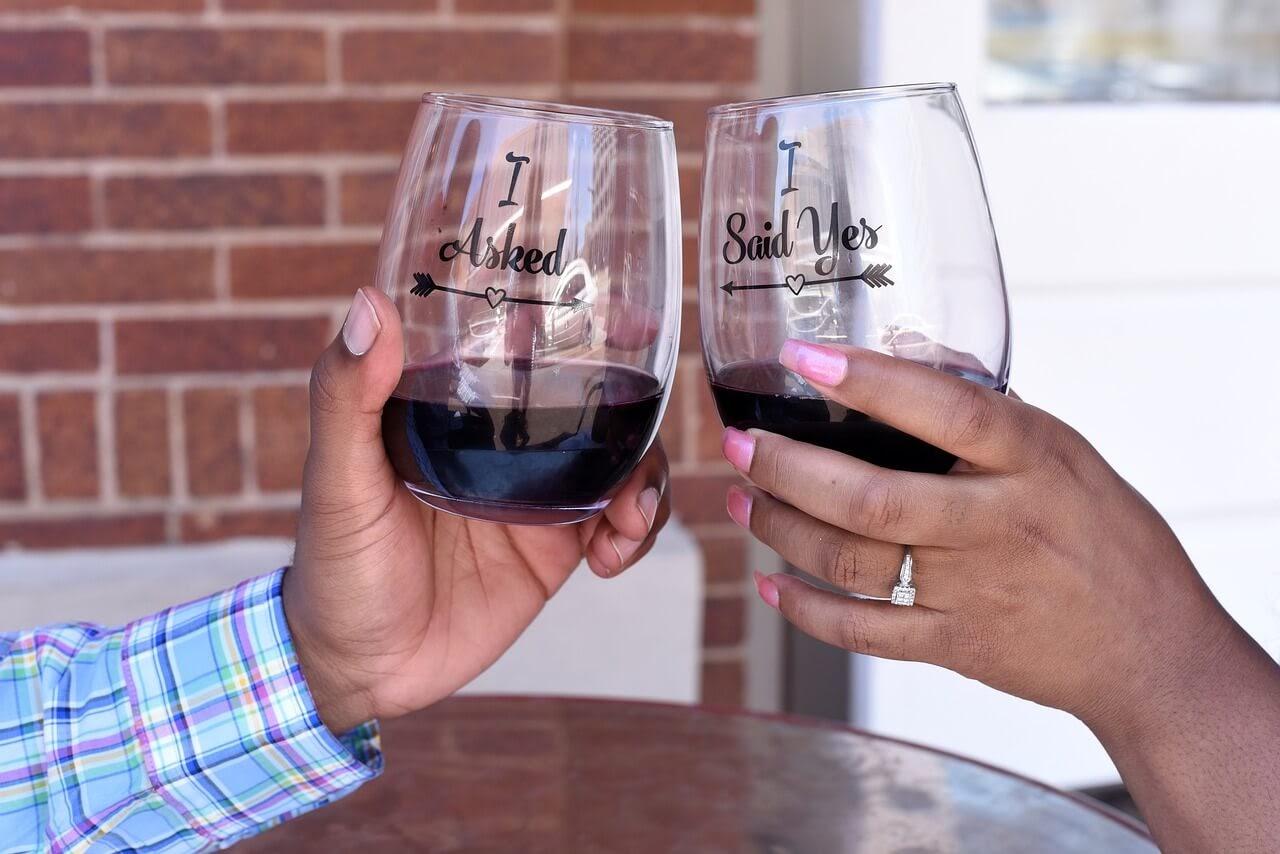 An engaged couple raises engagement wine glasses in celebration.