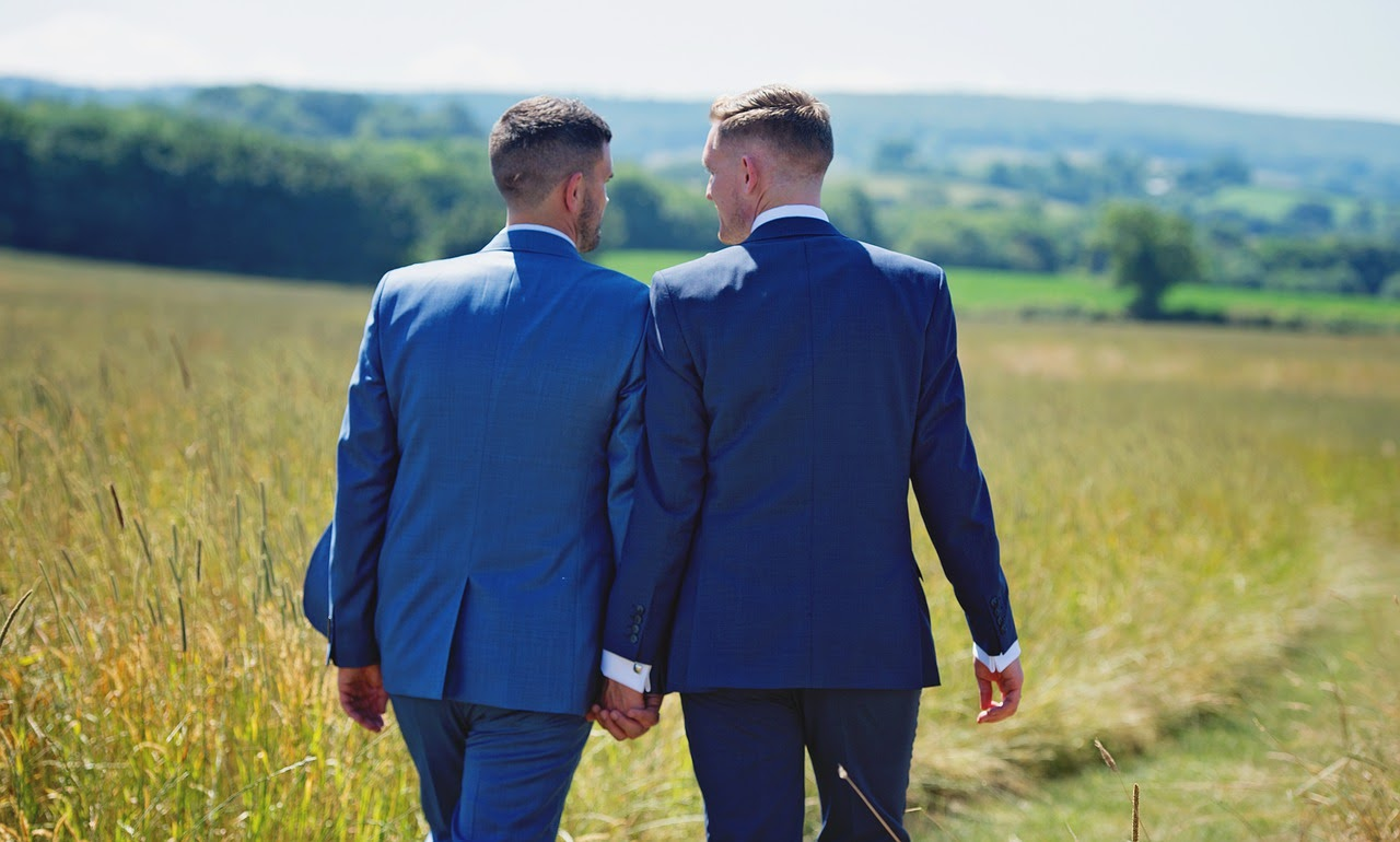 An engaged couple walks holding hands in a field.