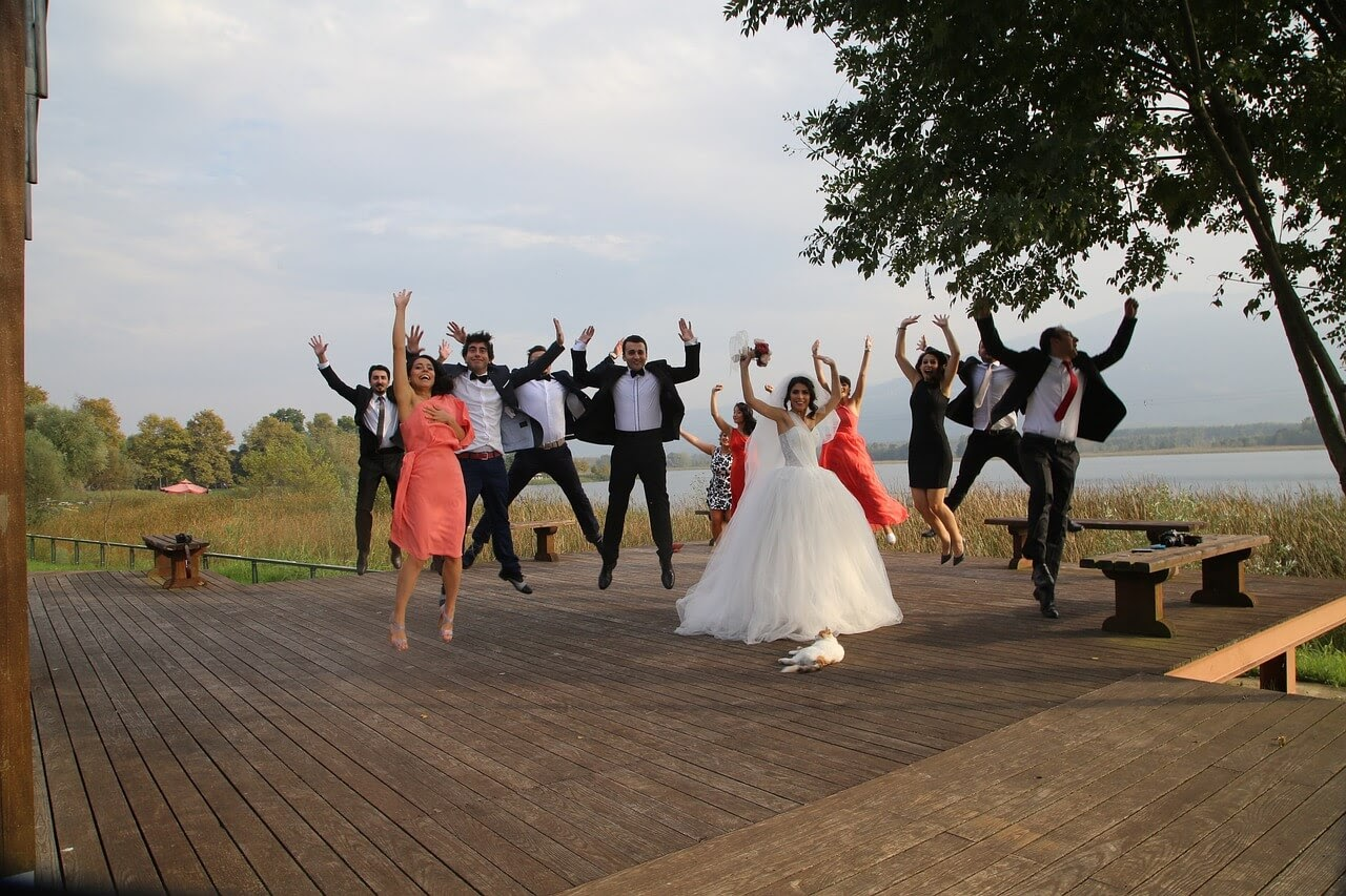 A wedding party jumps for joy for a picture.