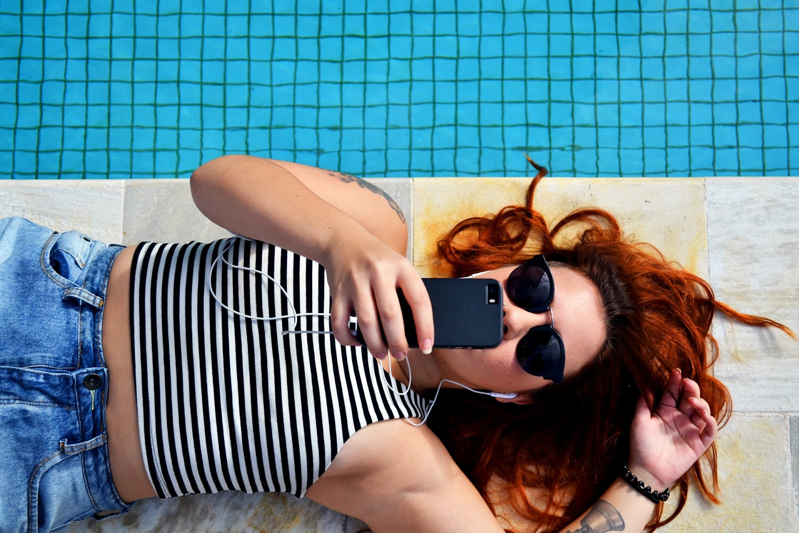a woman in her 20s lies by a pool as she swipes on a dating app