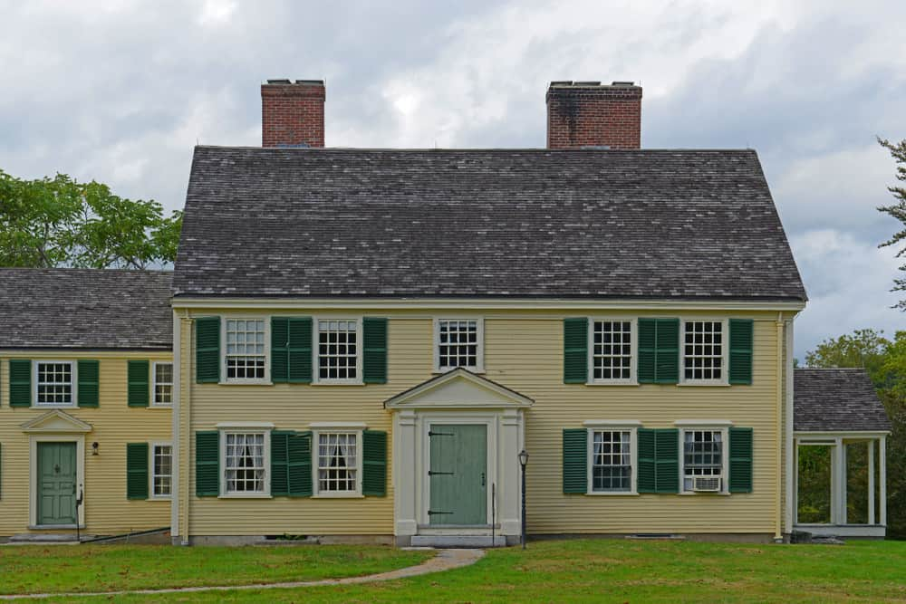 a yellow colonial revival home with green shutters available for purchase