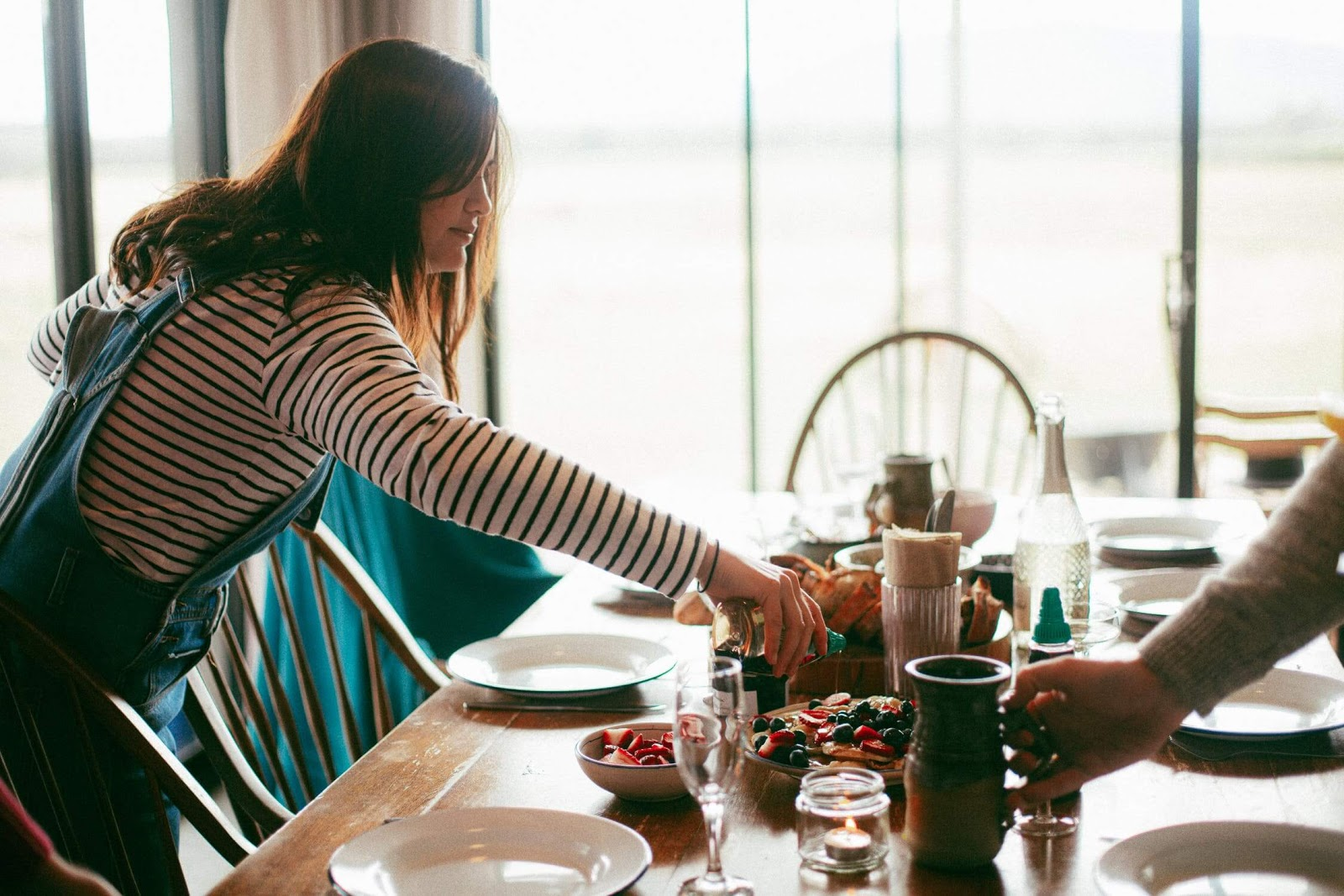 Woman prepares table of food for holiday gathering