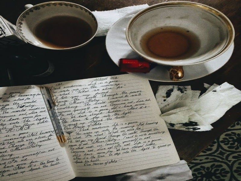 Several tea mugs and an open journal with writings all over it
