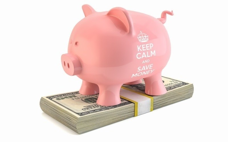 A piggybank sitting on top of a pile of money