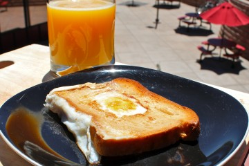 Photo of a piece of toast with a cooked egg in the middle and a glass of orange juice next to the toast