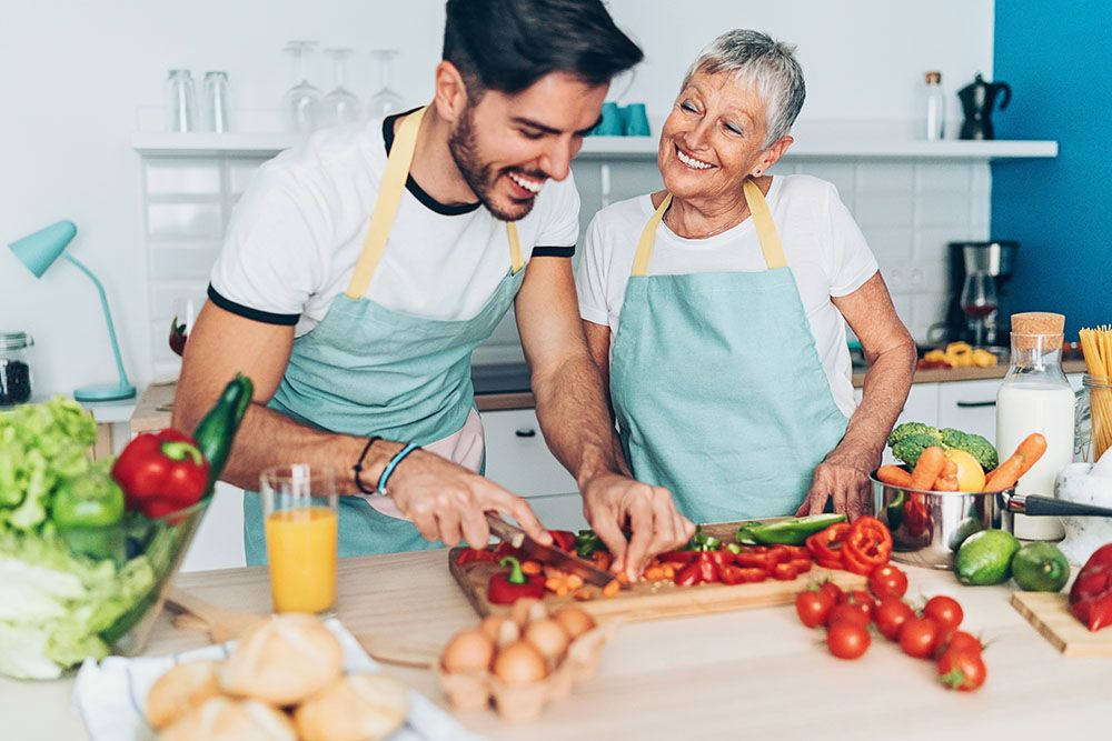 Picture of a man with an older woman in a kitchen cutting vegetables