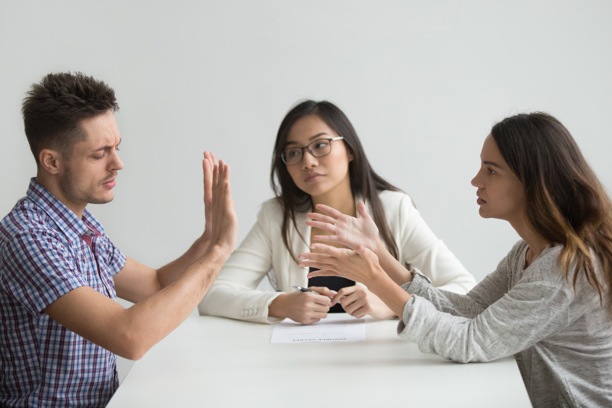 Photo of a man and woman arguing while a woman is sitting in the middle