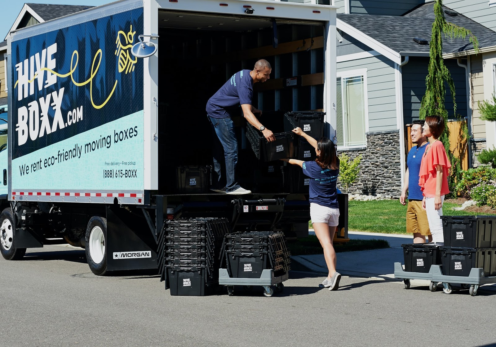 movers unloading boxes as the parents of a college graduate watch, smiling