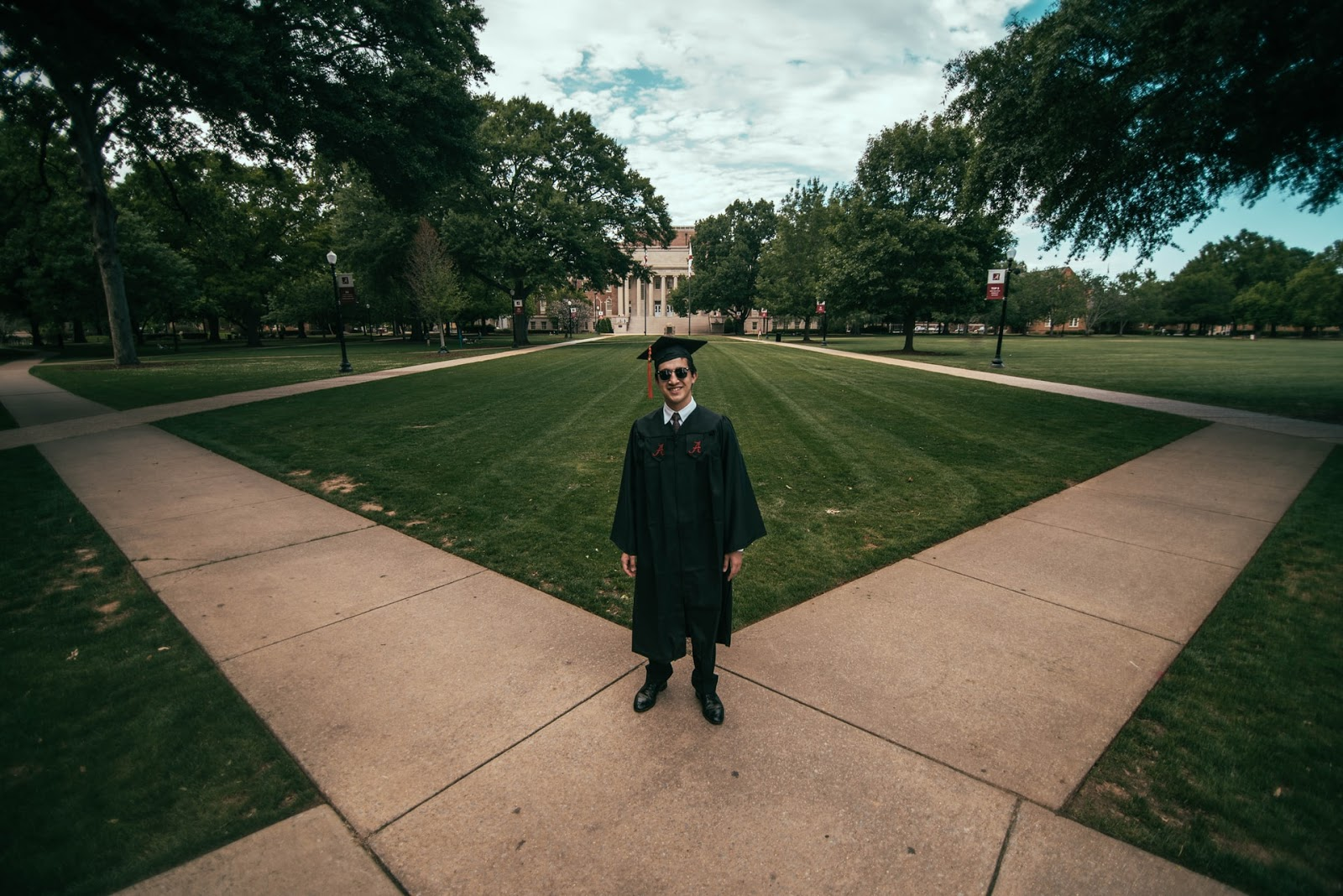 college graduate in a cap, gown, and sunglasses stands at the intersection of two sidewalks on the campus green