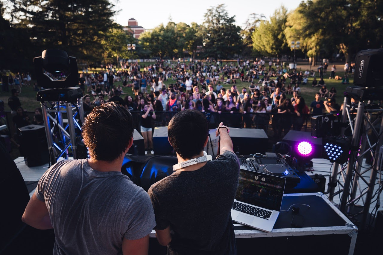 A view from the DJ's booth at a music festival, two DJ's gesture out at the crowd who have gathered on a lawn.