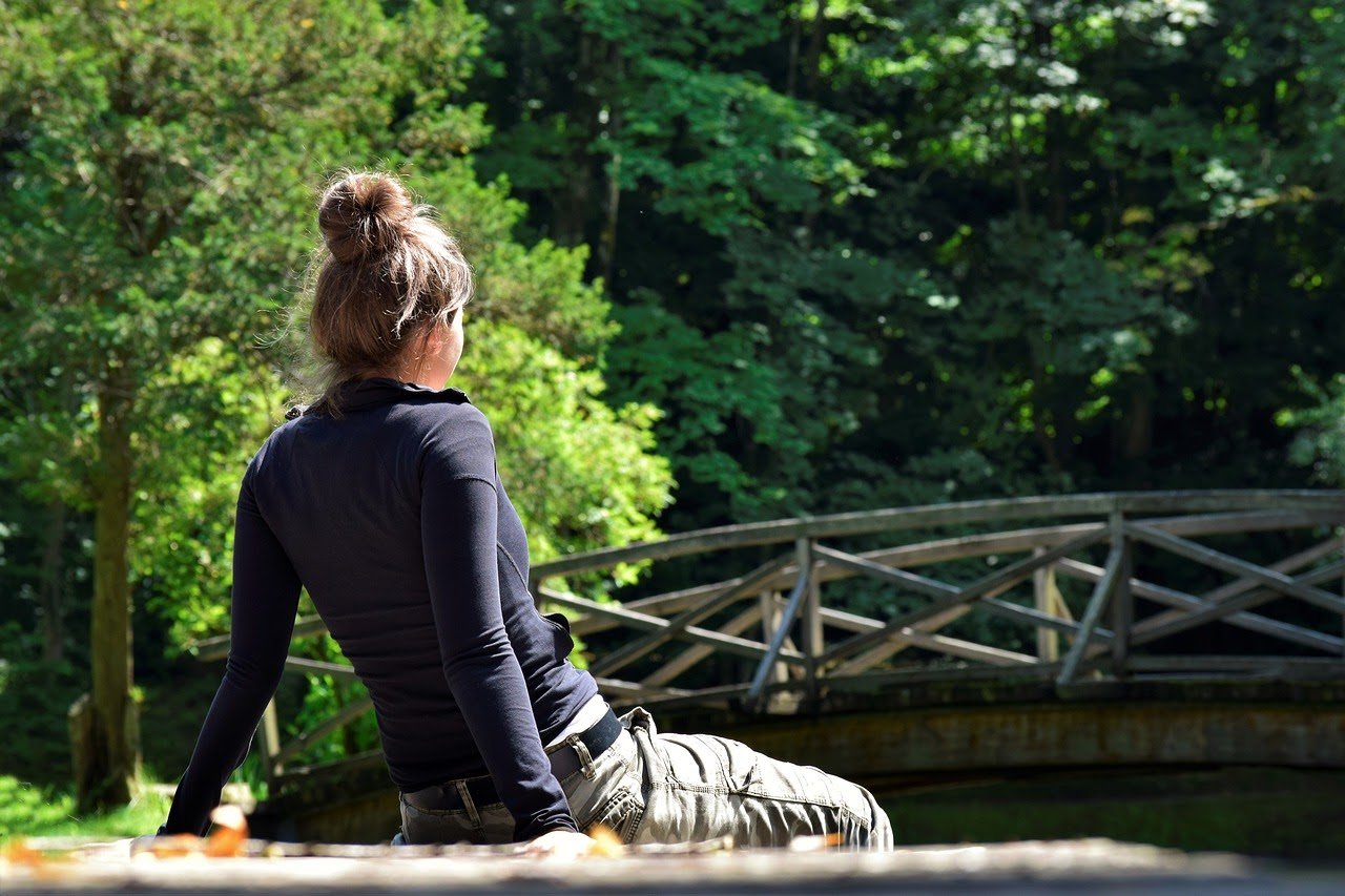 A woman with blonde hair sits on a ledge overlooking a river, in the background there is a foot bridge.