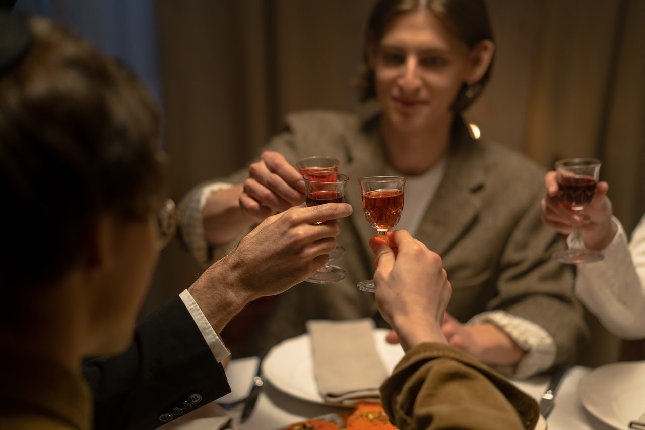 Friends gather around at a dinner table and raise their glasses of liquor together in a toast.