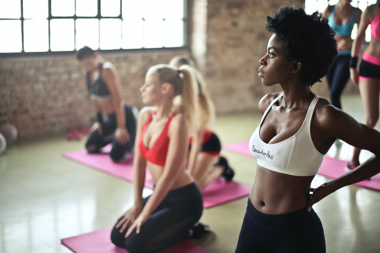 A group of women wait in a gym room for a yoga class. The woman closest to the camera is black,. She is wearing a white sports bra and black leggings.