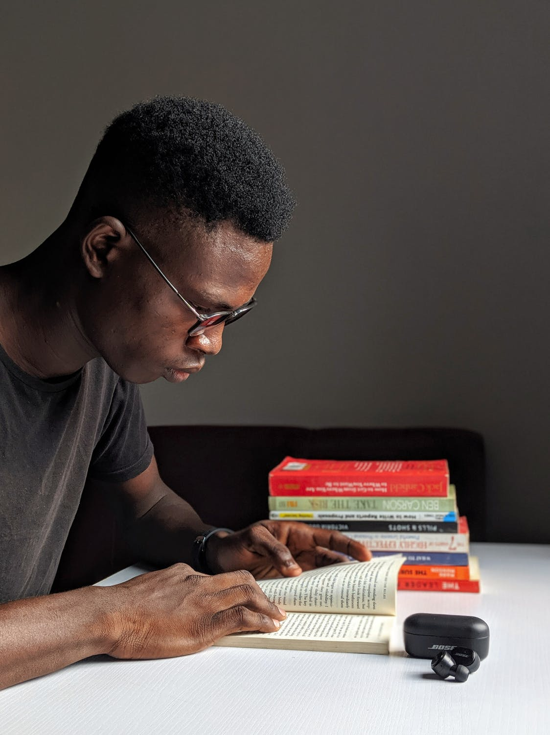 Male in his twenties reading a book at his desk