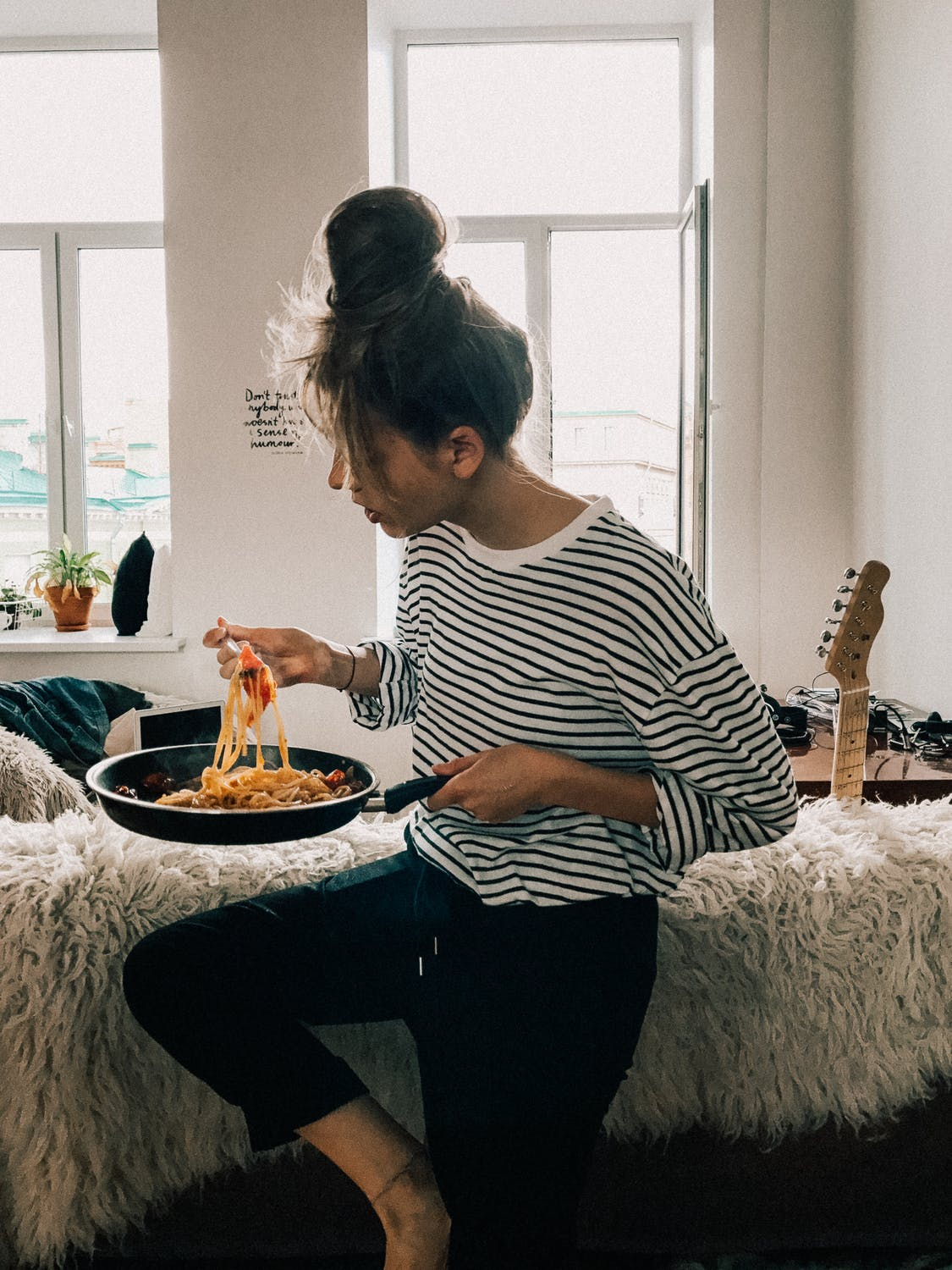 Girl in her college dorm casually eating pasta out of a pan