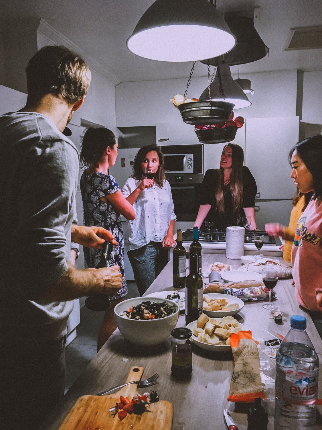 Group of friends stand around a kitchen island drinking wine and eating snacks