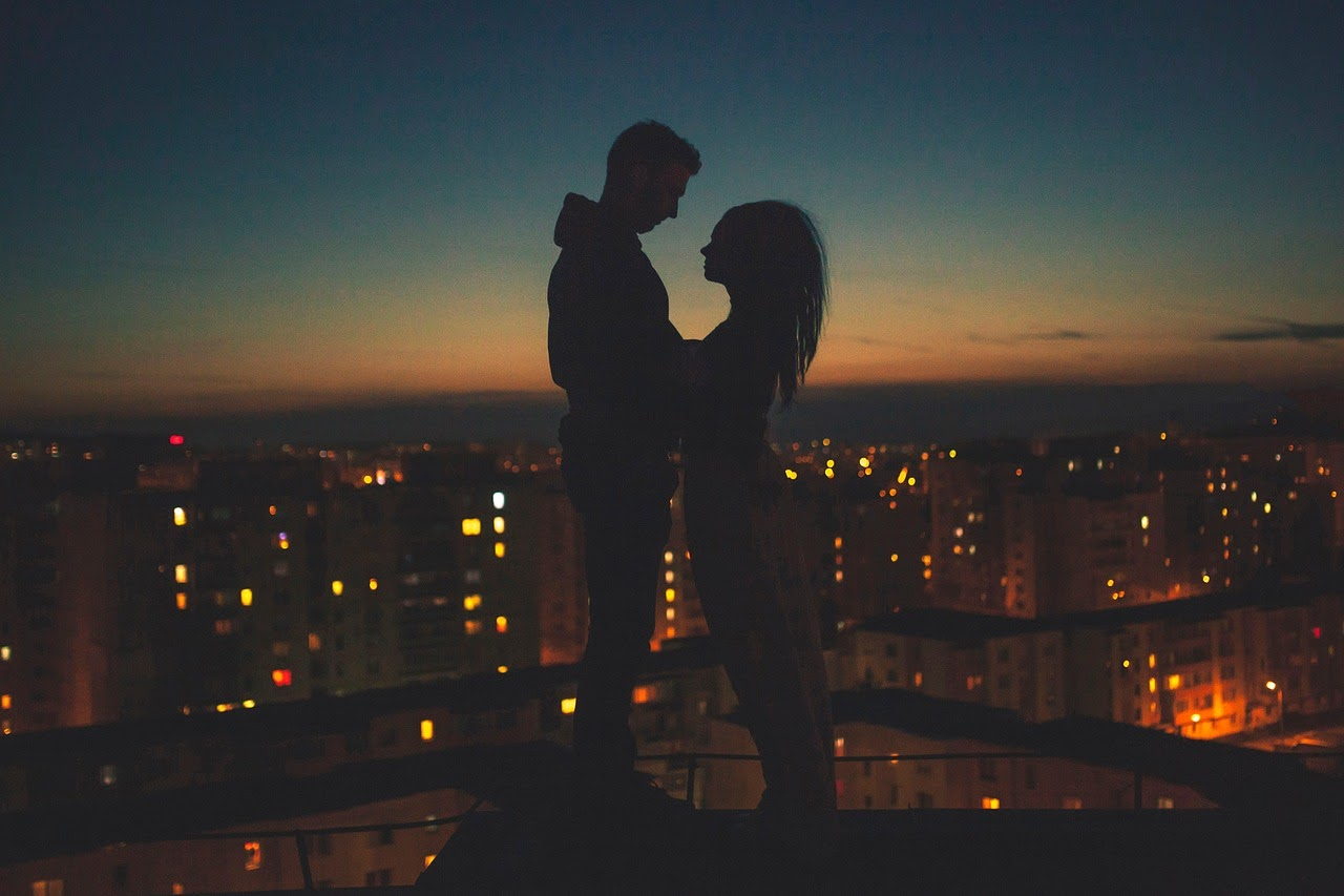 A man and a woman stand on a rooftop overlooking the city lights, their bodies are outlined in shadow.