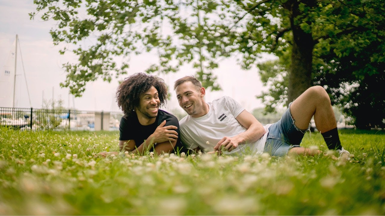Two guys, one white with brown hair, the other black with curly hair sit together in a field smiling.