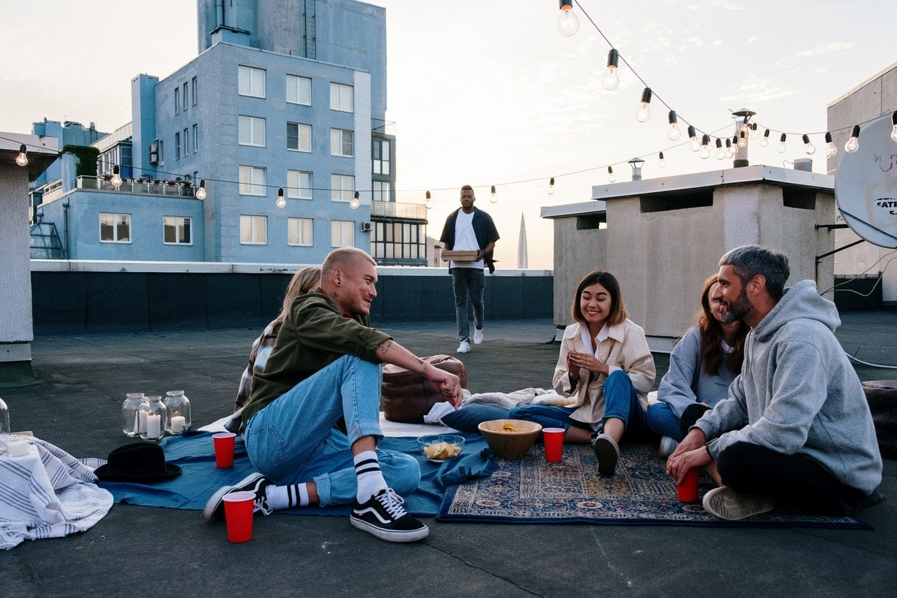 A group of people sit together for a picnic on a rooftop.