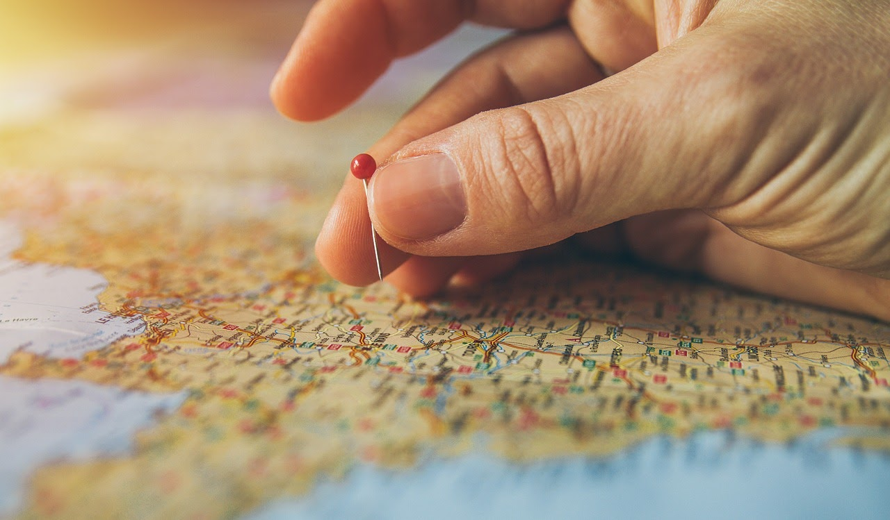 A closeup of a hand putting a red pin on a map.