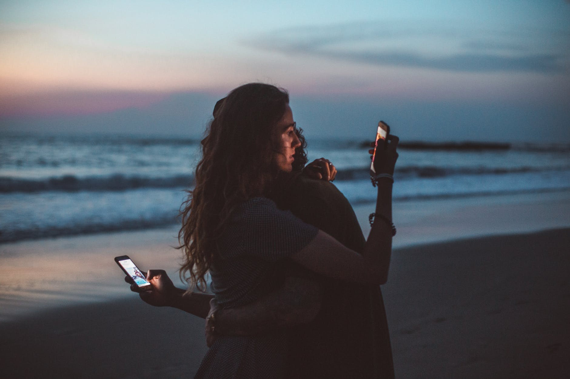 Two girl's standing on a beach staring at their cell phones