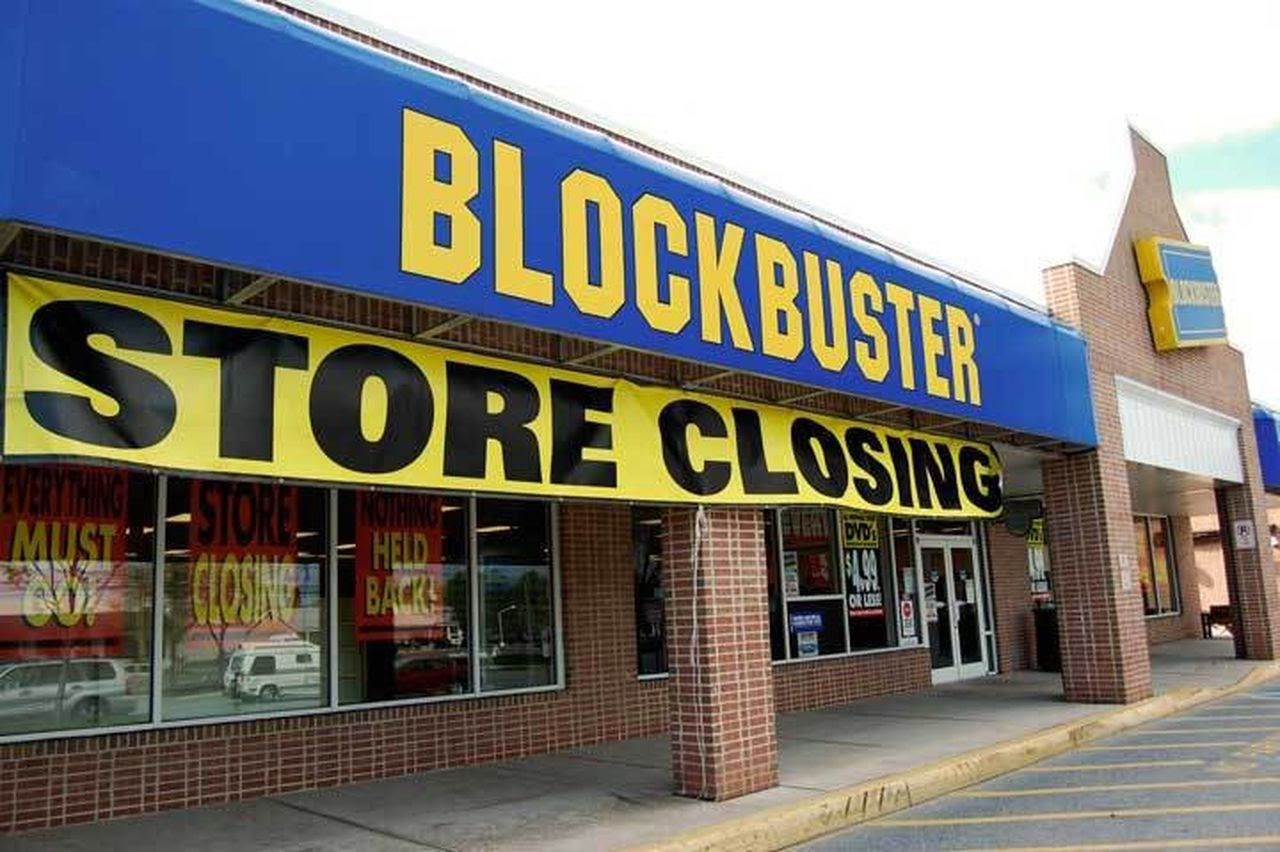 The outside of a Blockbuster store with a yellow closing sign across the front.