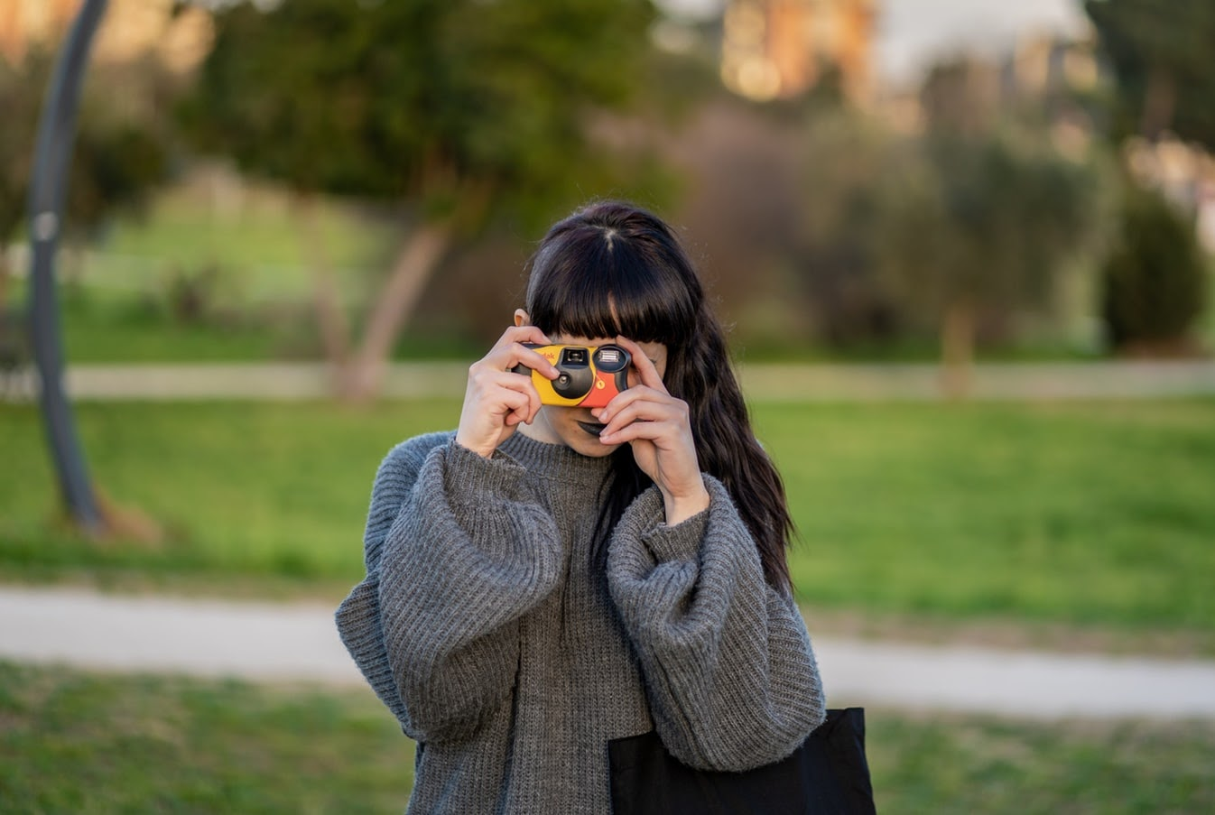 A woman taking a photo with a disposable camera.