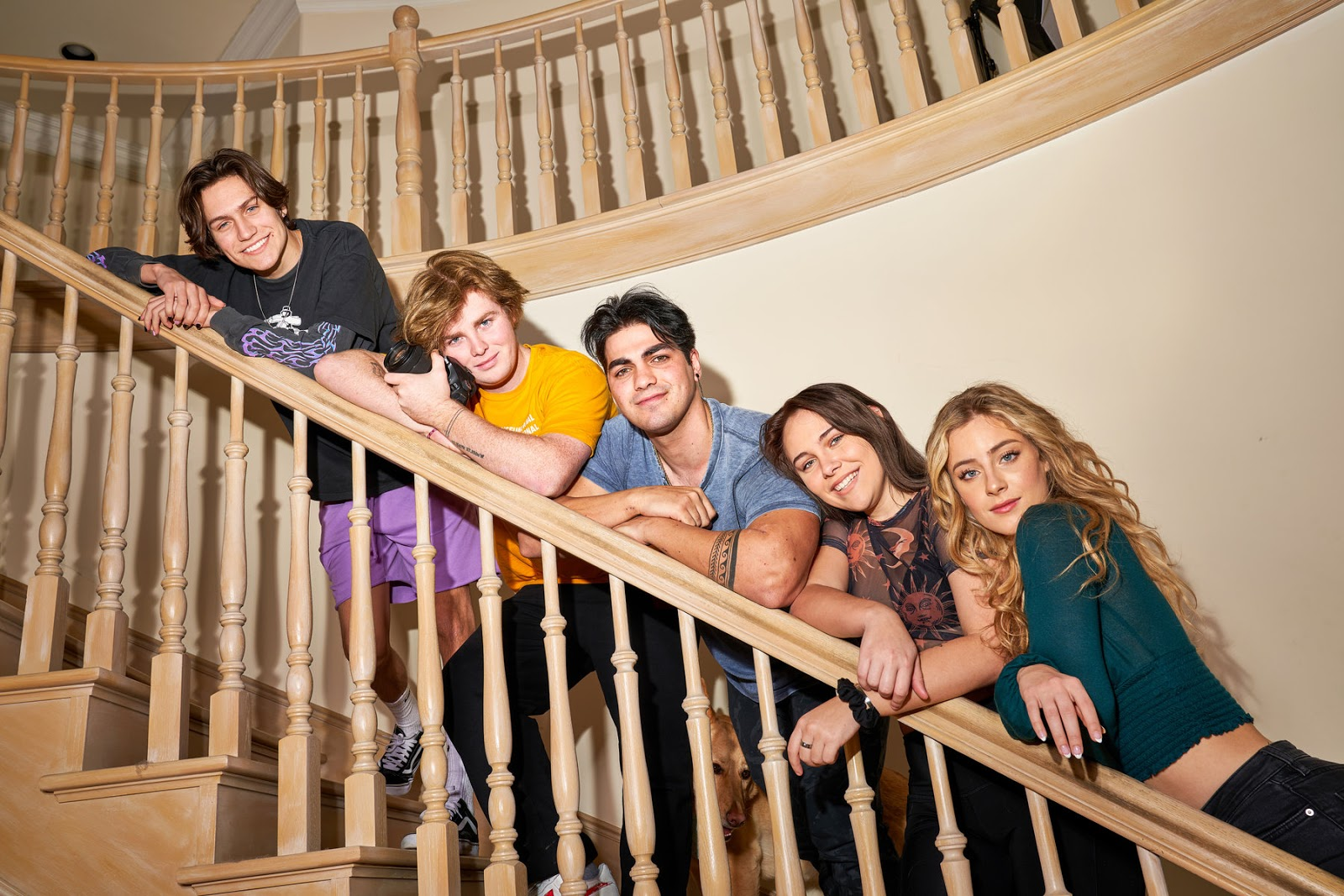 Five TikTok influencers standing on a staircase and leaning on eachother.