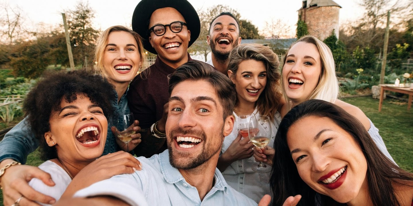 A group of millennials smiling at the camera.