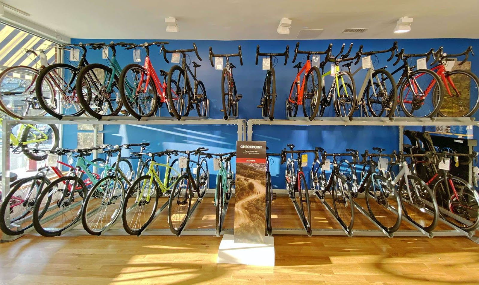 An assortment of colorful bikes on shelves in a bike shop.