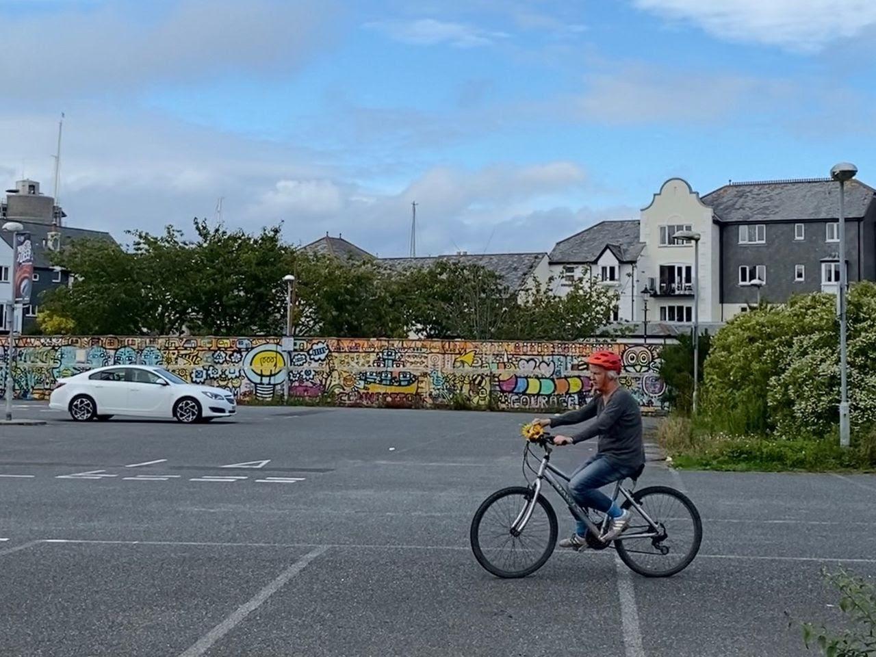 A man riding a bike in a parking lot.