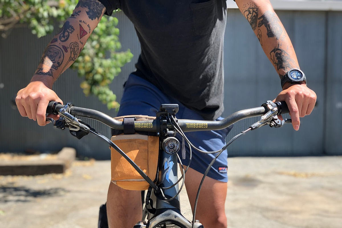 A closeup of a man holding the handle bars of a bike.