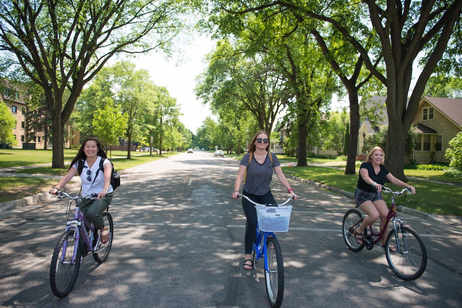 Three young women riding bikes down a street.