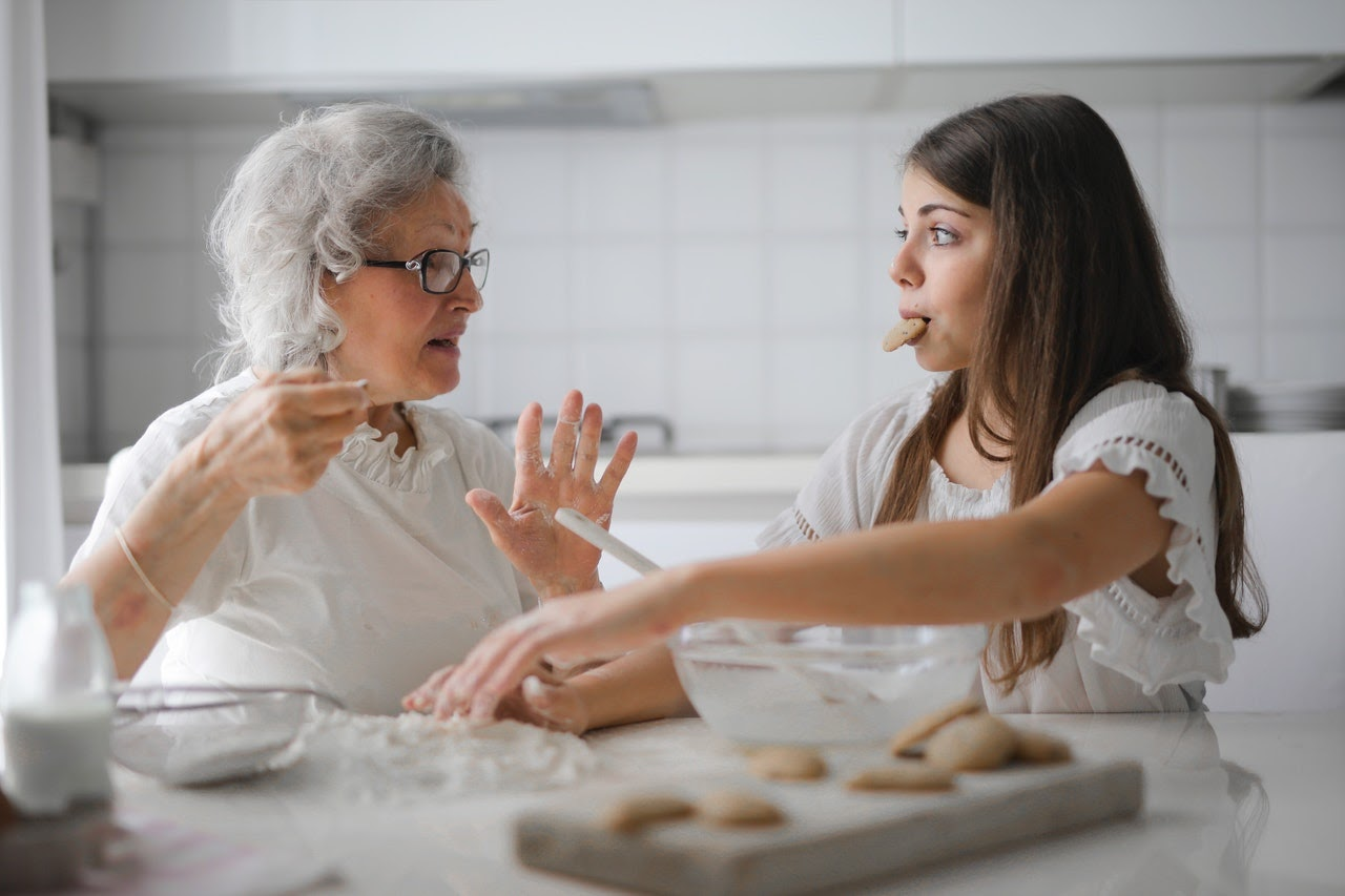An older woman and her daughter sit at a kitchen counter making cookies. The daughter has a cookie in her mouth.