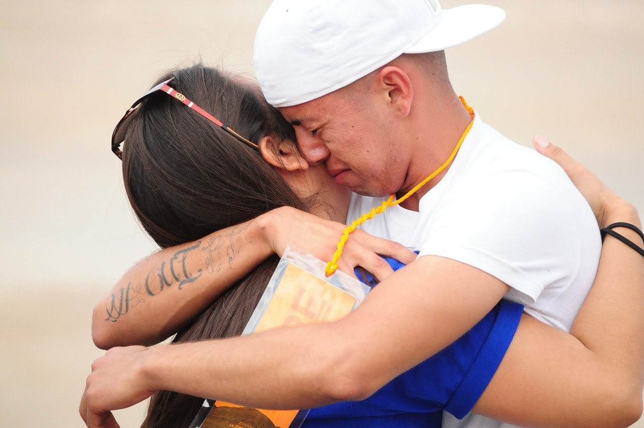 A mother and son share a tearful embrace.