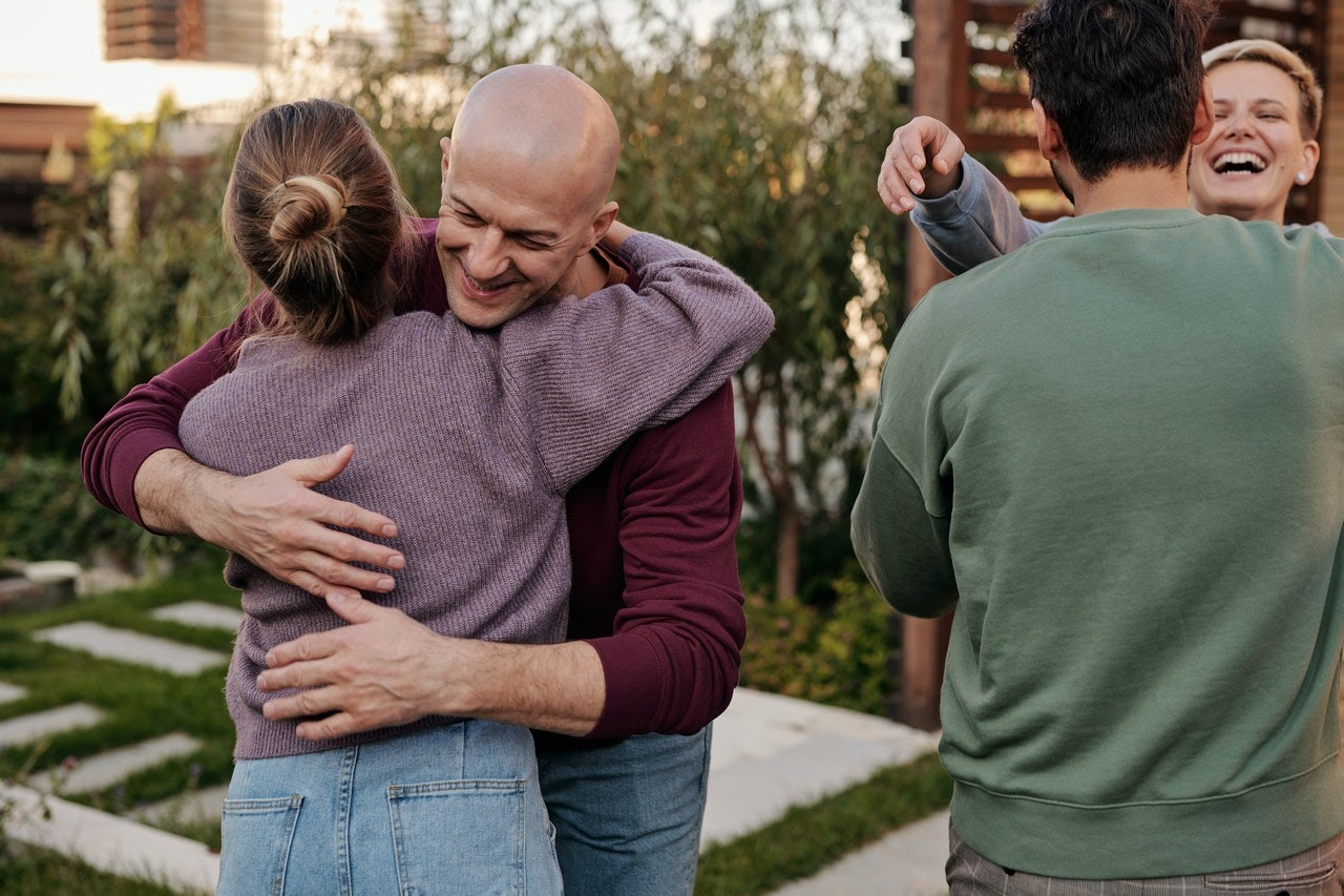 A younger pair of people and an older pair of people share welcomign embraces.