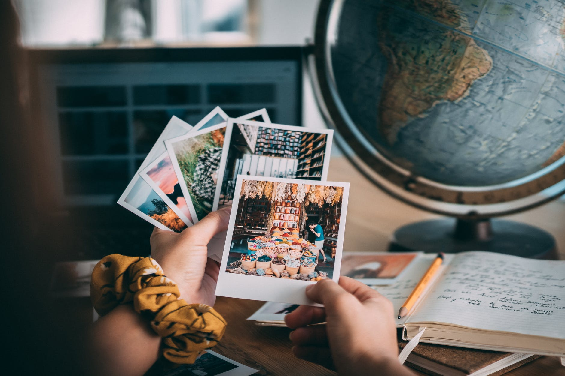 Millennial looking at old polaroid photos to reminisce on the past