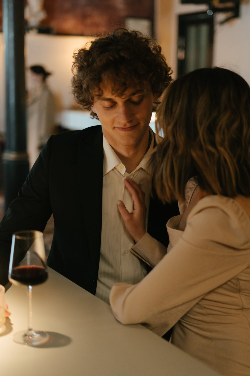 Woman gently touches the chest of her date as they sit at a bar in a restaurant.