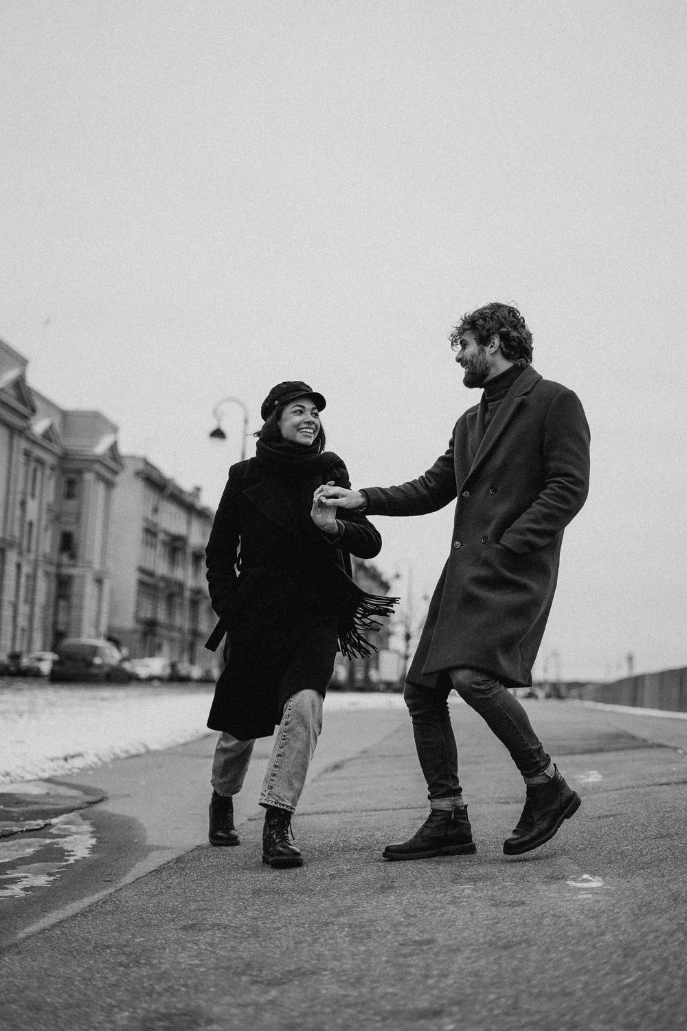 Black and white image of a couple smiling at each other as they join hands on the sidewalk.