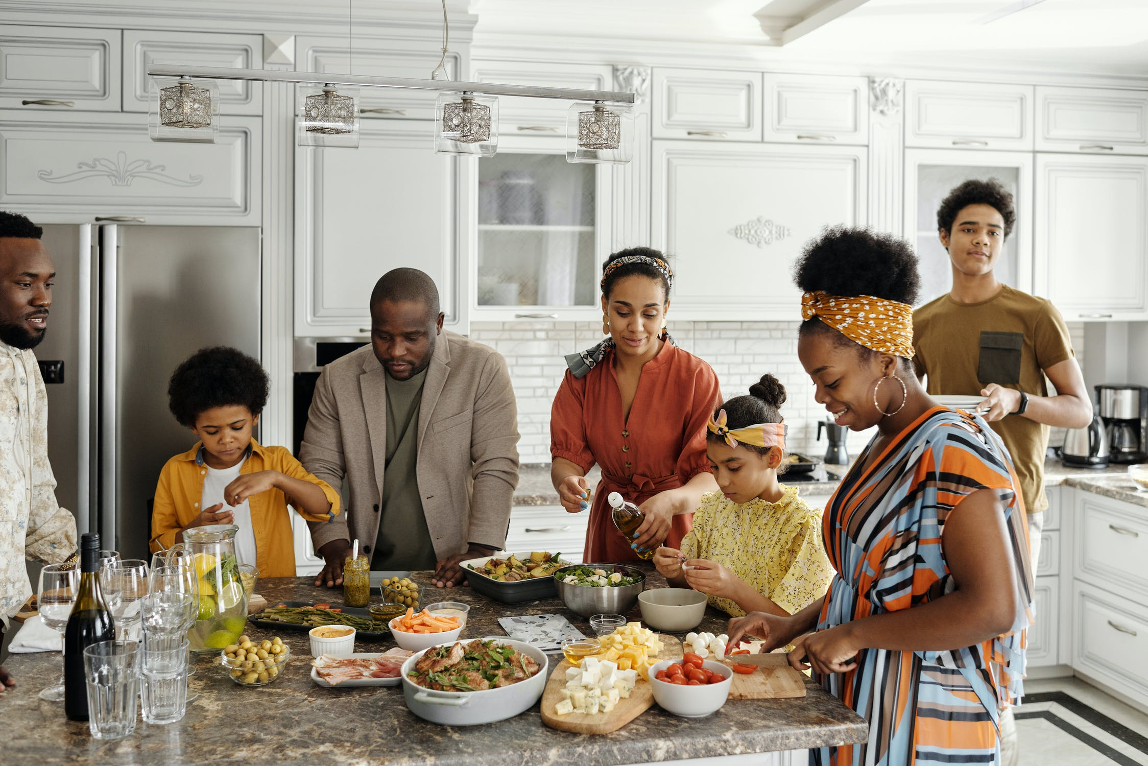 Family gathers around a kitchen island piled high with food.