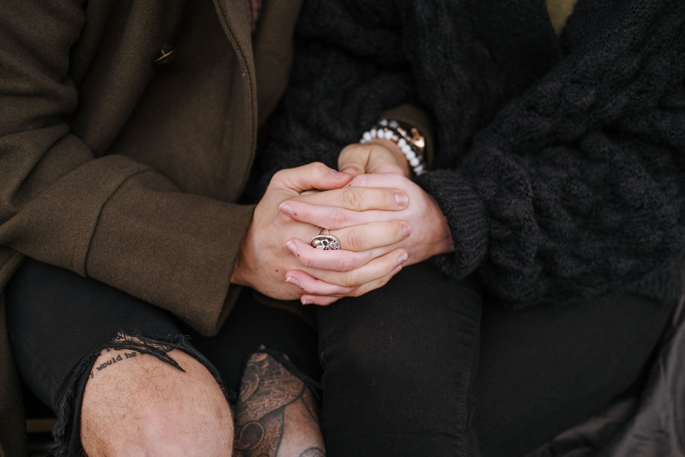 Couple's joined hands rest on their laps as they sit.