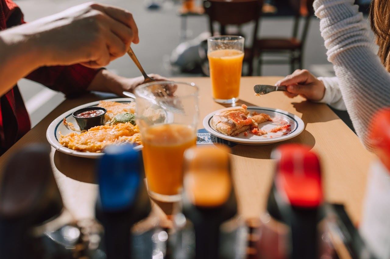 A closeup of a lunch table where two people are eating their meals and drinks.