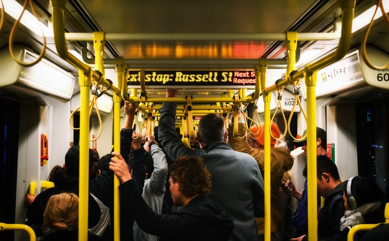 A shot of a crowded subway car. People are packed in shoulder to shoulder.