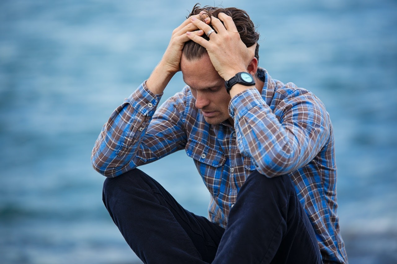 A man sits on the edge of a pier with his hands in his hair, frustrated.