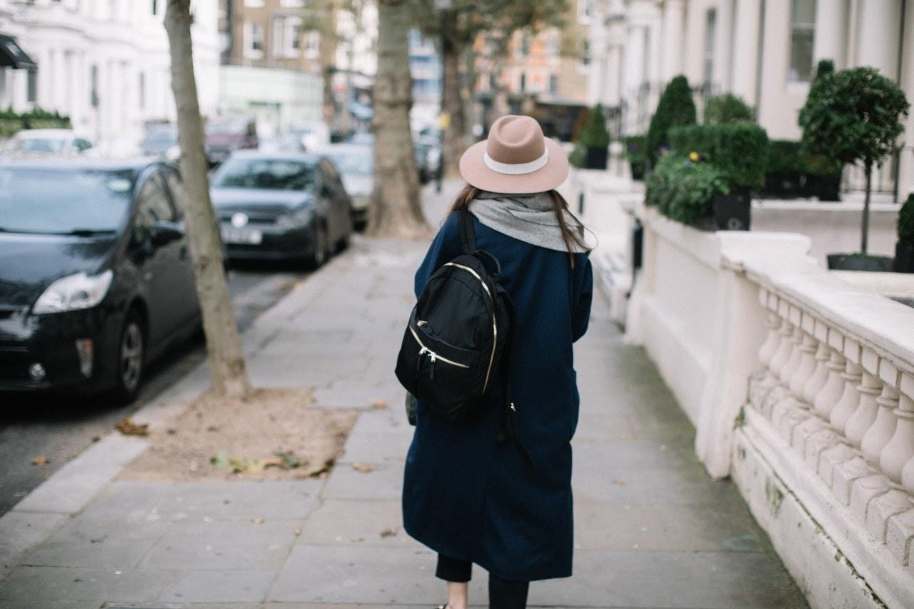 A woman in a pink hat walks on the sidewalk.