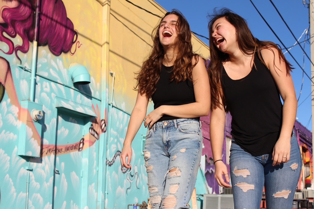 Two woman walk down an alleyway with a painted mural on it. They're laughing.