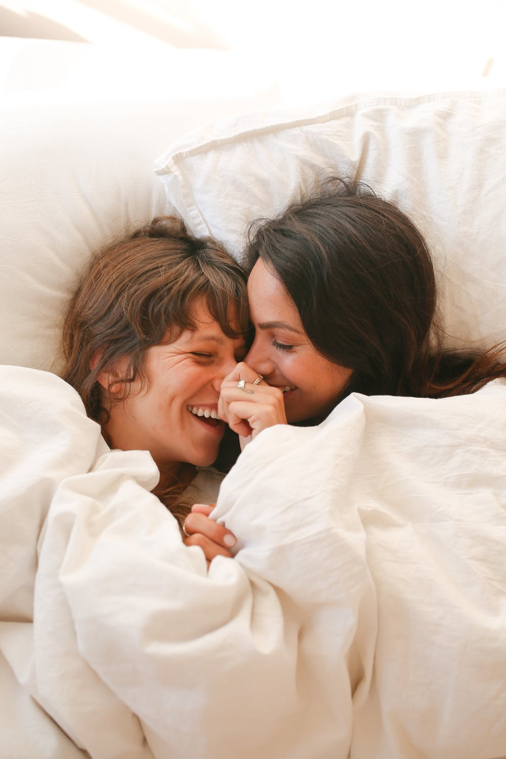 A couple laughs in each other's arms on a bed with white sheets.