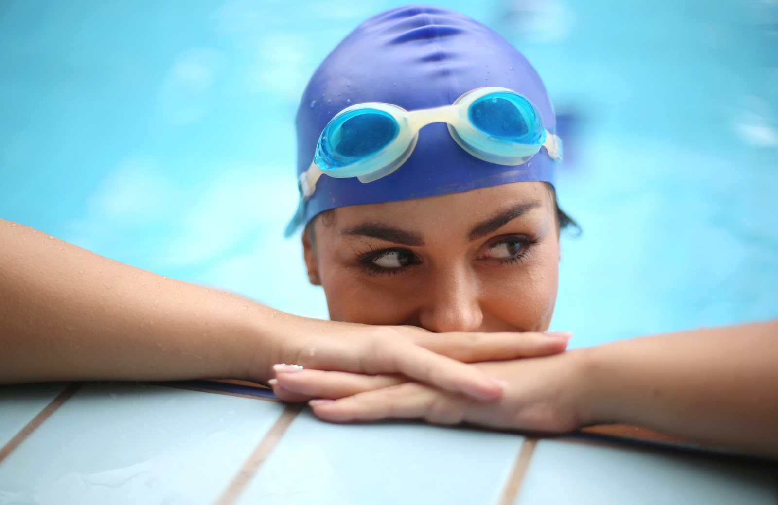 A woman with a swim can and goggle resting both hands on a pool deck